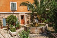Sikt av huset som vänder mot en fyrkant med springbrunnen i Châteaudouble Royaltyfri Foto