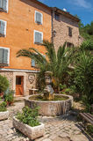 Sikt av huset som vänder mot en fyrkant med springbrunnen i Châteaudouble Fotografering för Bildbyråer