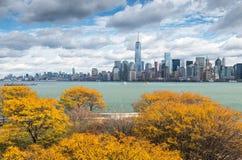 Sikt av i stadens centrum Manhattan från Ellis Island med höstliga träd Royaltyfria Foton