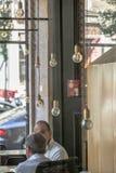 Sikt av inre på stången, med två män som talar, och retro dekorativa ljus arkivbild