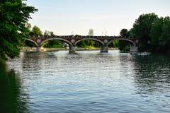 Sikt av Isabella Bridge som korsar Poet River på skymning med några kanotister som paddlar och gör sportar Arkivfoton