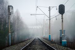 Sikt av järnvägen, trafikljus och elektriska poler i dimma i vår royaltyfri foto