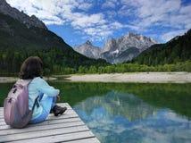 Sikt av Julian Alps med flickasammanträde på pir i Slovenien Royaltyfri Fotografi