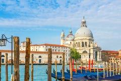 Sikt av kanalen som ?r stor med historiska basilikadi Santa Maria della Salute i bakgrunden och gondolerna Venedig, Italien arkivfoton