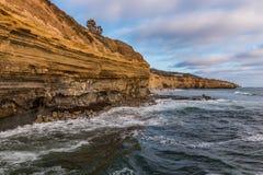 Sikt av klippor och stranden på högvatten, solnedgångklippor Fotografering för Bildbyråer