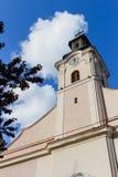 Sikt av klockatornet med klockan av katolska kyrkan med bakgrund för blå himmel Royaltyfria Bilder