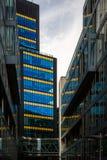 Sikt av kontors- och affärsbyggnader med blåa och gula fasader för exponeringsglasfönster royaltyfri fotografi