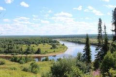 Sikt av krökningen av skogfloden från den höga banken Royaltyfri Foto