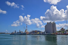Sikt av kustbevakningskytteln och fabriksbyggnad från Caudan strand, Port Louis, Mauritius Fotografering för Bildbyråer