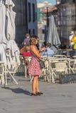 Sikt av kvinnan som så använder mobiltelefonen i gatan, med resväskan och kameran i hand, utvikningsbrudstil, utomhus- terrass me royaltyfri fotografi