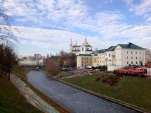 Sikt av kyrkan och byggnaderna bak floden som täckas med is, mot den blåa himlen med moln Vitebsk Vitryssland royaltyfri fotografi
