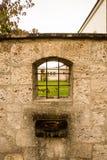 Sikt av kyrkaträdgården till och med ett fönster Royaltyfri Bild
