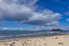 Sikt av Lobos från den Corralejo stranden med dramatiska cloads Arkivfoto