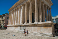 Sikt av Maisonen Carrée med folk, en forntida romersk tempel i Nimes Royaltyfria Bilder