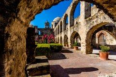 Sikt av meditationträdgården till och med en gammal stenbåge på den historiska gamla västra spanska beskickningen San Jose Arkivfoto