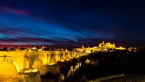 Sikt av Mezquita, Catedral de Cordoba, över den roman bron på solnedgången royaltyfri fotografi