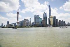 Sikt av modern Pudong horisont vid Huangpu River mot molnig himmel Arkivbild