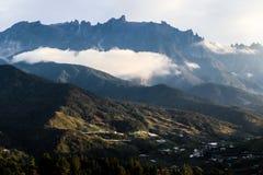 Sikt av Mount Kinabalu i morgonen med låg nivåmolnet och den lilla byn i avståndet royaltyfri bild