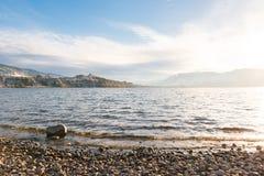 Sikt av Okanagan sjön i vinter från den tre mil stranden med Penticton och berg i avstånd arkivfoton