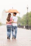 Sikt av par tillbaka under att gå för paraply Royaltyfri Foto