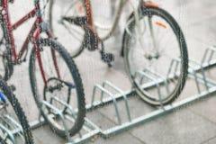 Sikt av parkerade cyklar till och med exponeringsglaset med droppar av vatten Royaltyfri Fotografi