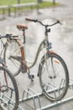 Sikt av parkerade cyklar till och med exponeringsglaset med droppar av vatten Royaltyfria Bilder