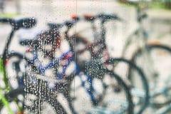 Sikt av parkerade cyklar till och med exponeringsglaset med droppar av vatten Arkivbilder