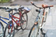Sikt av parkerade cyklar till och med exponeringsglaset med droppar av vatten Royaltyfri Foto