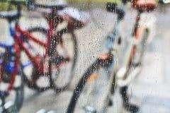 Sikt av parkerade cyklar till och med exponeringsglaset med droppar av vatten Arkivfoton