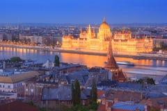 Sikt av parlamentet som bygger som är upplyst på skymning, Budapest Arkivfoto