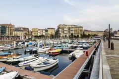 Sikt av porten av San Sebastian, Donostia med fartyg av fiske och staden till botten spain Arkivfoto
