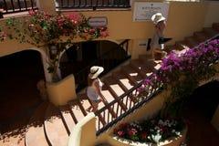 Sikt av Porto Cervo med två kvinnor med en sugrörhatt det gå på en trappuppgång Royaltyfri Bild
