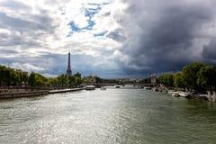 Sikt av Seinet River med Eiffeltorn i bakgrunden, med dramatiska himlar över staden france paris Royaltyfria Foton