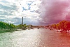 Sikt av Seinet River med Eiffeltorn i bakgrunden, med dramatiska himlar över staden france paris kulört Royaltyfria Foton