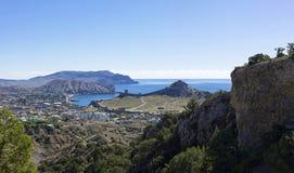 Sikt av semesterortstaden av Sudak och den medeltida Genoese fästningen från en berglutning arkivfoto