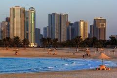 Sikt av Sharjah från stranden av Al Mamzar Solnedgång royaltyfri bild