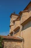 Sikt av sidoväggen och kyrkakyrktorn i morgonsolen i Figanières Arkivbild