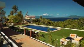 Sikt av simbassängen ovanför palmträd, havet och den tropiska ön, Puerto Galera lager videofilmer