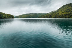 Sikt av sjön med mörkt turkosvatten med liten vågor och moun Royaltyfri Bild