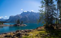 Sikt av sjön Minnewanka i de steniga bergen Arkivbild