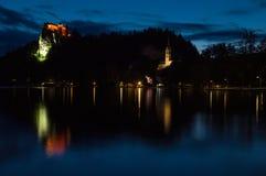 Sikt av sjön och den blödde slotten, solnedgång, reflexion av slotten i sjön, Slovenien Royaltyfri Foto