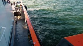 Sikt av skeppdäcket med dettäckt golvet, vinschen, kablar och vatten för lugna hav som kraschar mot shipboard stock video