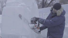 Sikt av skulptören som snider is rörelse Klipp is med en chainsaw Klipp och gör isskulptur Hugga av is med en yxa arkivfilmer