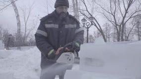 Sikt av skulptören som snider is rörelse Klipp is med en chainsaw Klipp och gör isskulptur Hugga av is med en yxa lager videofilmer