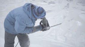 Sikt av skulptören som snider is rörelse Klipp is med en chainsaw Klipp och gör snöskulptur Hugga av med is vatten med Fotografering för Bildbyråer