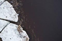 Sikt av smältande isisflak i lerigt flodvatten med avskräde i vår royaltyfria foton