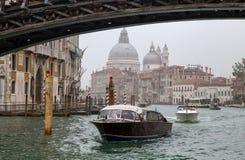 Sikt av små färjor på kanalen som är stor i en dimmig dag med historiska basilikadi Santa Maria della Salute i bakgrunden i Ven arkivbild