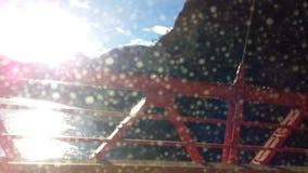 Sikt av solen på solnedgången från en bro mellan berg royaltyfria bilder