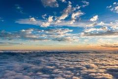 Sikt av solnedgången ovanför molnen Arkivbilder