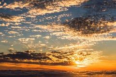 Sikt av solnedgången ovanför molnen i bergen Arkivbilder